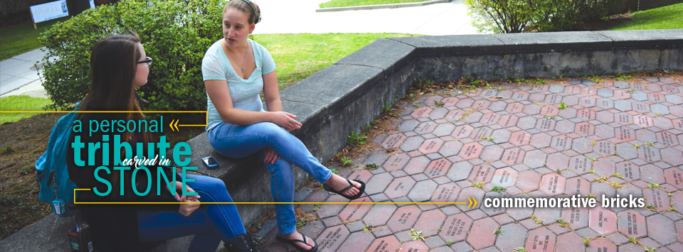 a personal tribute carved in stone, commemorative bricks. Image of two students sitting on the wall around the brick courtyard.
