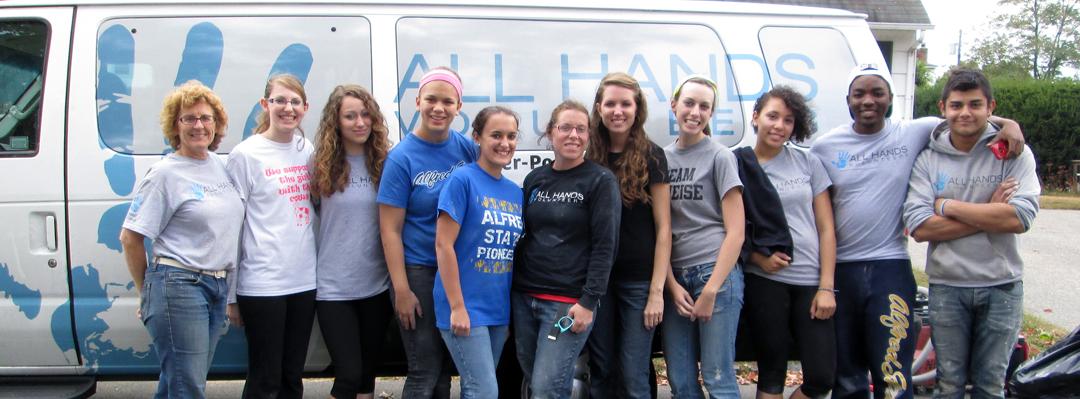 several all hands volunteers standing in front of a van