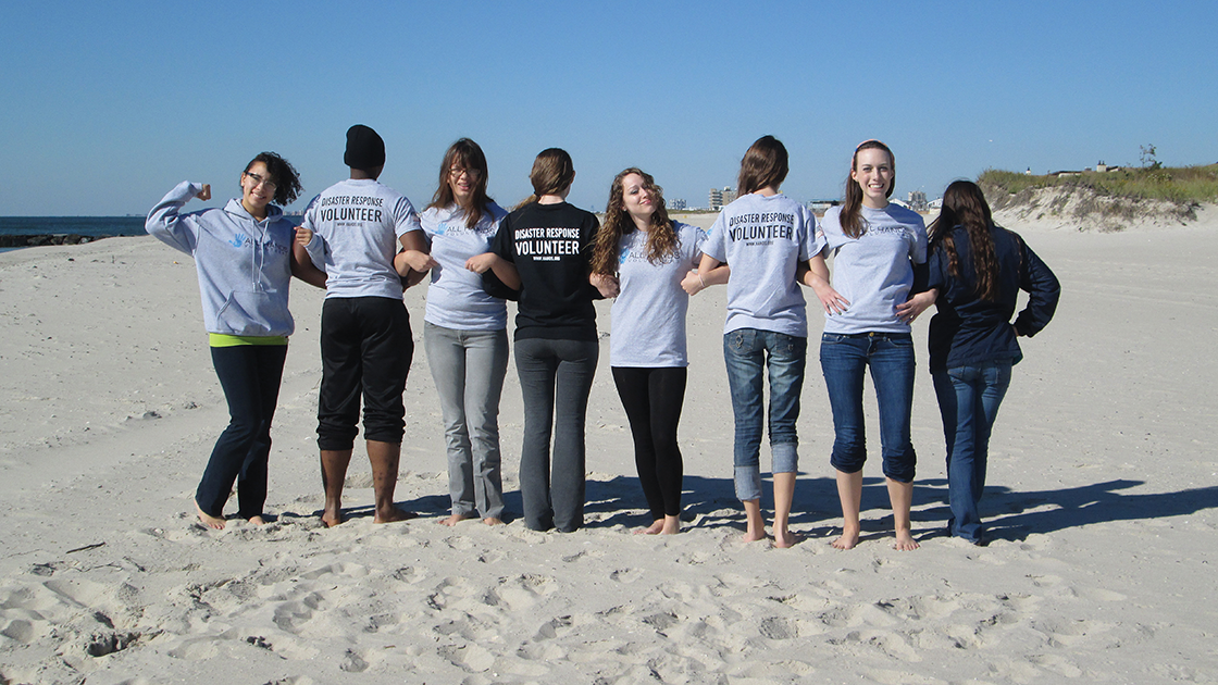 several students on a beach wearing disaster response volunteer t-shirts