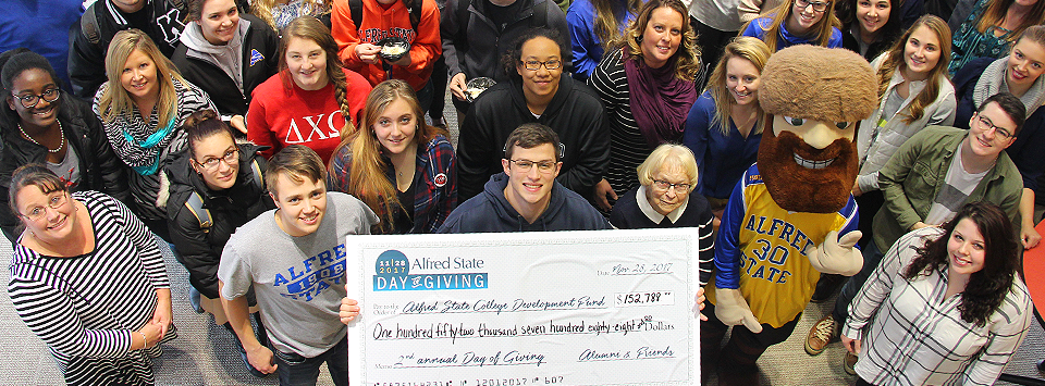 11-28-2017 DAY OF GIVING. Image of excited students and staff celebrating a successful day of giving with a large check showing $152,788