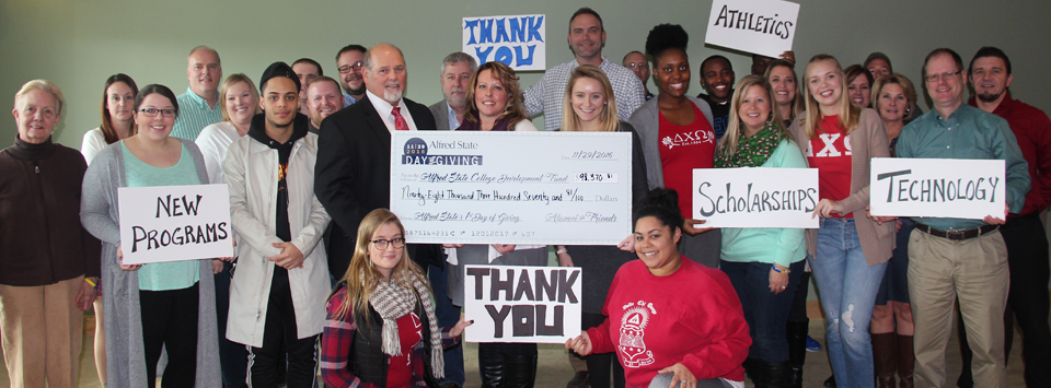 Image of students, faculty, and star presenting a $98,370.81 Day of Giving total check to President Sullivan.