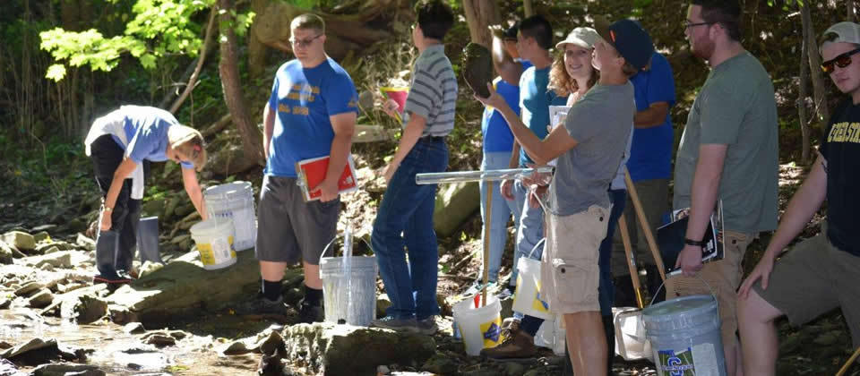 group of students with buckets in a creek