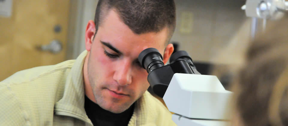 male student in front of a microscope