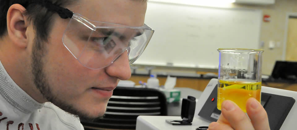 male student looking into a beaker with yellow liquic