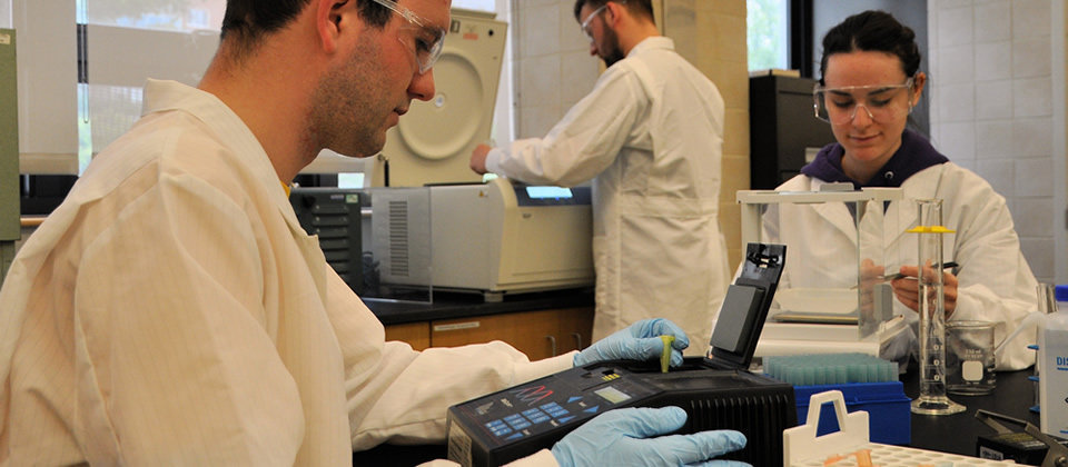 3 students in a lab wearing white coats, blue gloves, using testing equipment