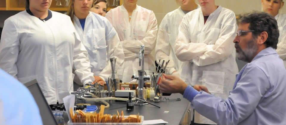 students in white lab coats watching a professor demonstrate something in lab