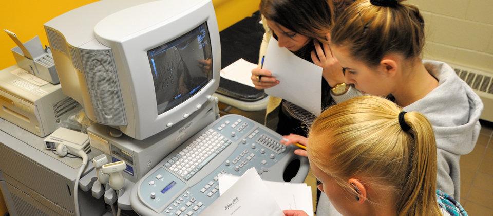 three female students around a sonography machine