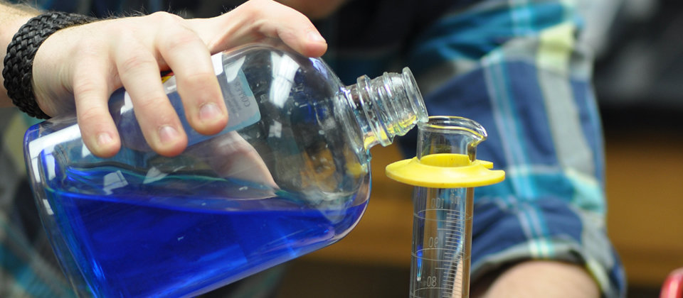 male student hands with cup of blue liquid pouring into a beaker