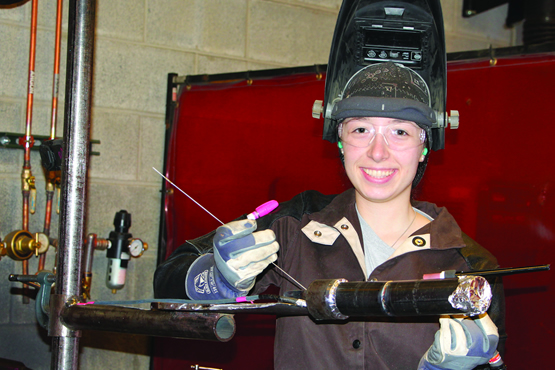 Deborah Huppman holding some welding equipment wearing a helmet