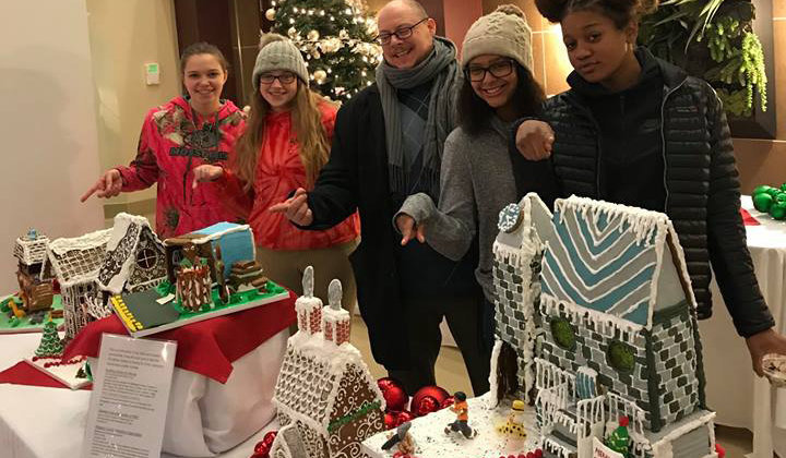 students standing behind their gingerbread houses