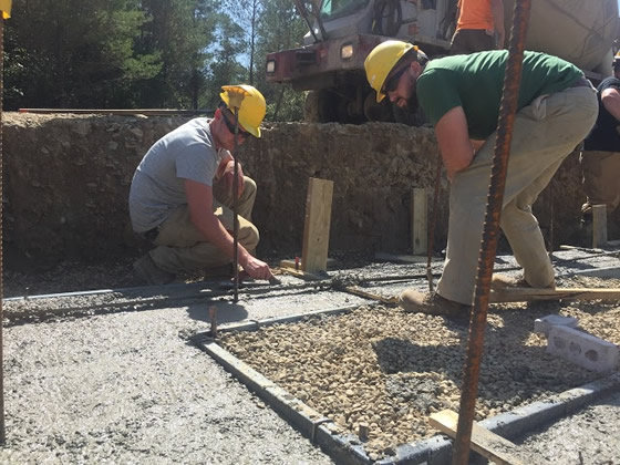 students pouring concrete, wearing hard helmets