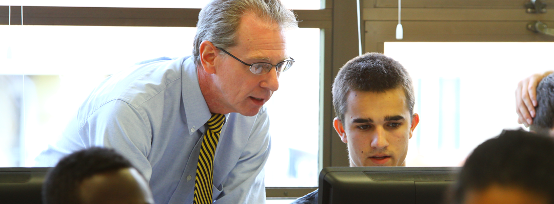male professor looking over the shoulder of male student at a computer