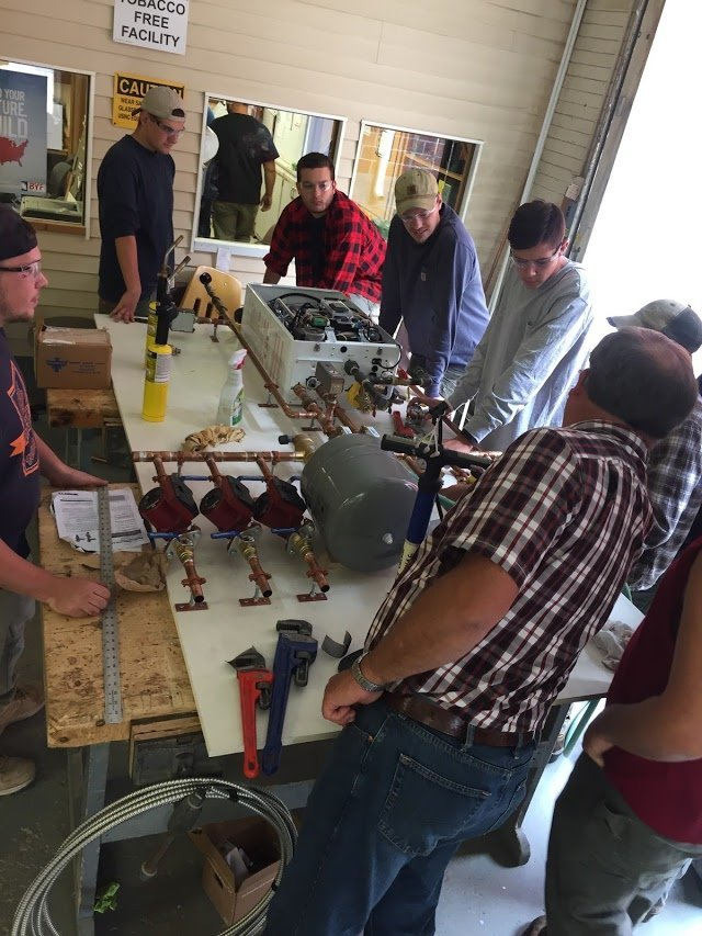students in a lab looking at pipes and wiring on a board