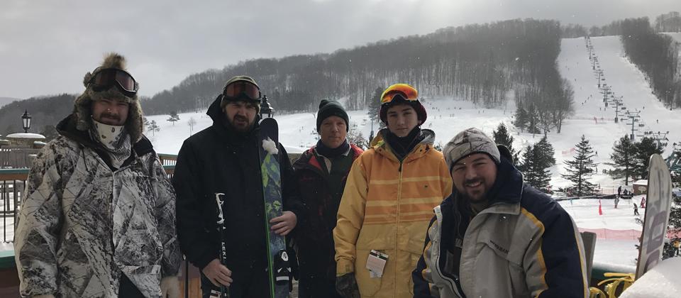 five males at a ski resort wearing coats and hats