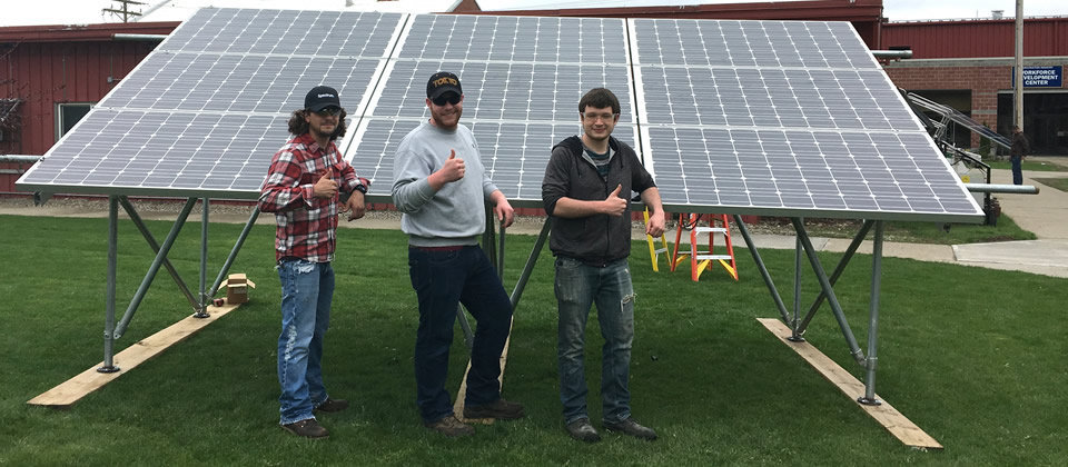 three male students in front of a solar panel on campus