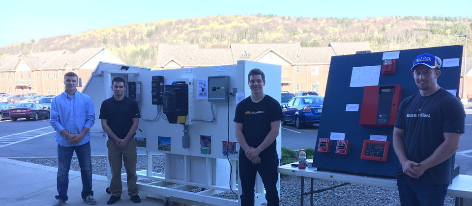 students standing in front of their projects at student showcase