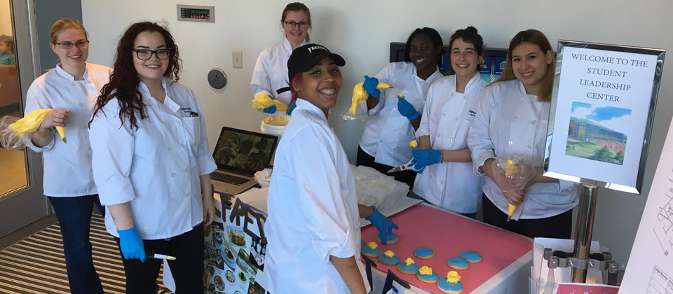 students frosting cookies at a table