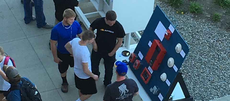 two male students standing outside showing off a fire alarm system