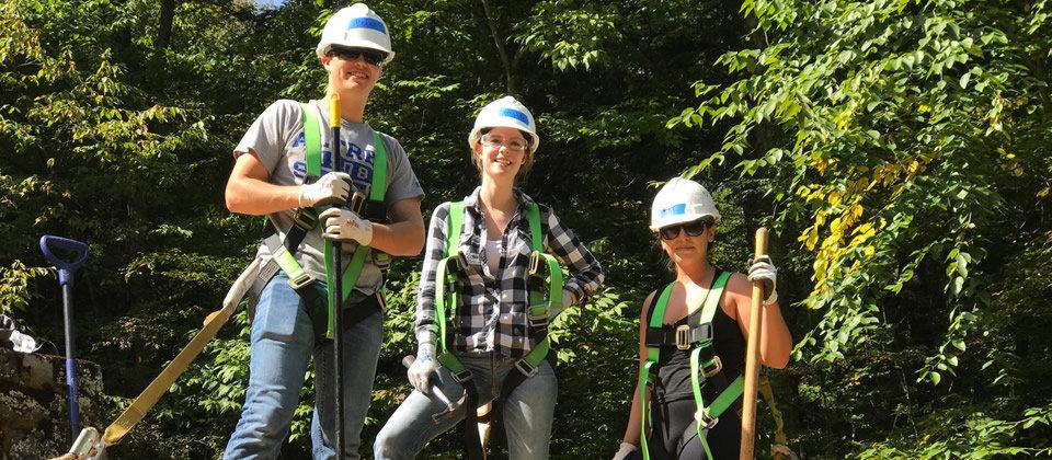 three students wearing hard helmets