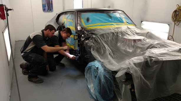 two male students working on a car