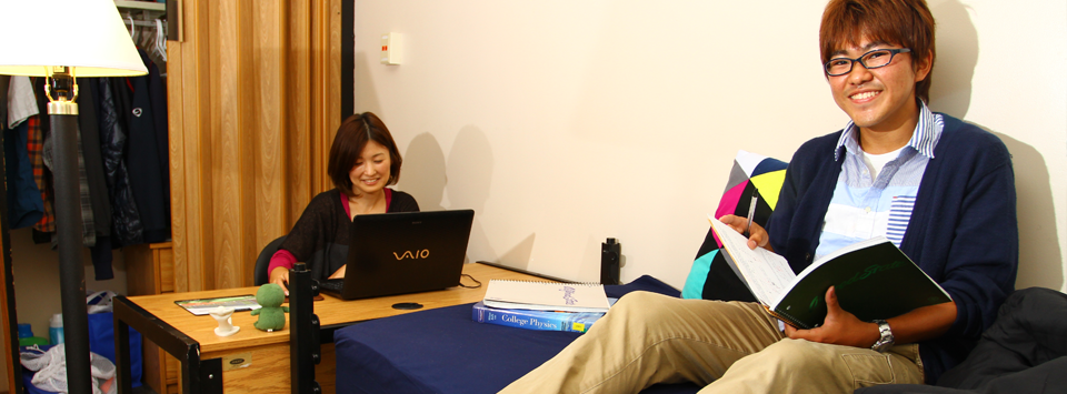 female student sitting at a desk and male student sitting on a bed in residence hall