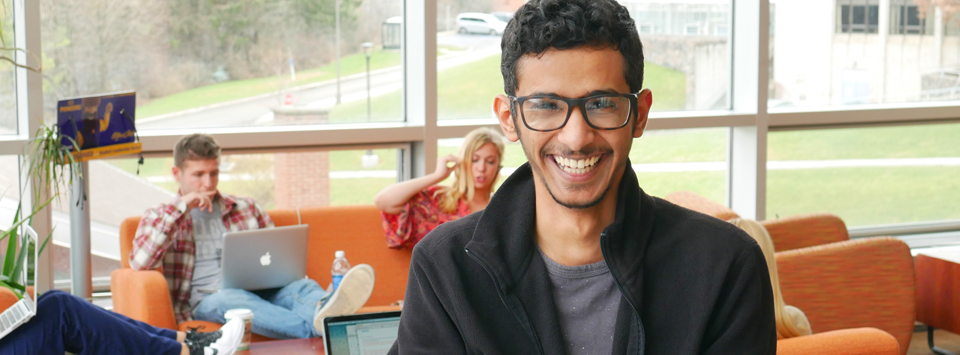 Male international student laughing as friends study behind him at Student Leadership Center