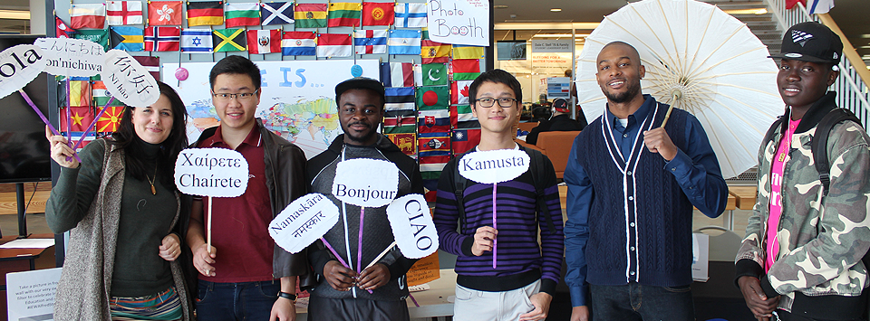 International club members pose for a photo holding signs with greetings in multiple languages.