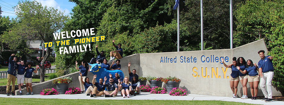 Welcome to the Pioneer Family! Image of Orientation Mentors posing at the campus entrance with our mascot.