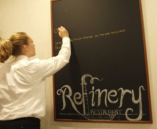 student writing on a chalkboard, 'Refinery'