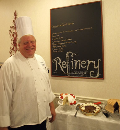 chef near the chalkboard sign that says Refinery