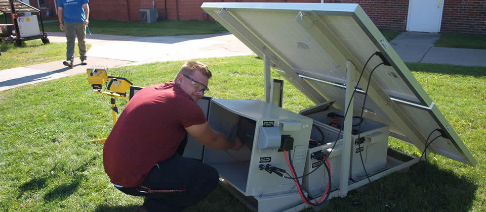 student working on a solar panel
