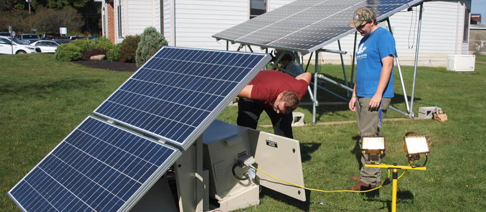two students working on a solar panel