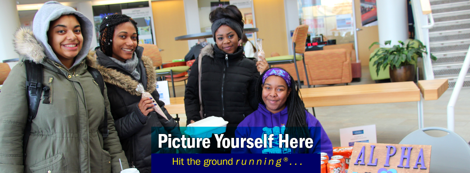 Four females pose for the camera in the SCL near Alpha Sigma's valentine table. Text reads Picture yourself here, Hit the ground running®...