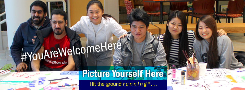 "International club members pose for a photo. Text reads""Picture yourself here, hit the ground running®... #YouAreWelcomeHere"