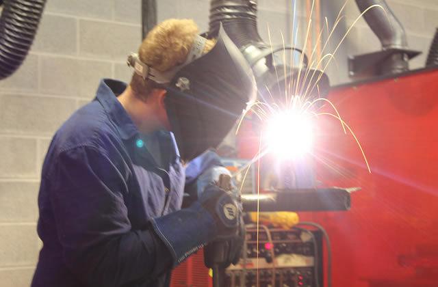 student wearing welding helmet, welding
