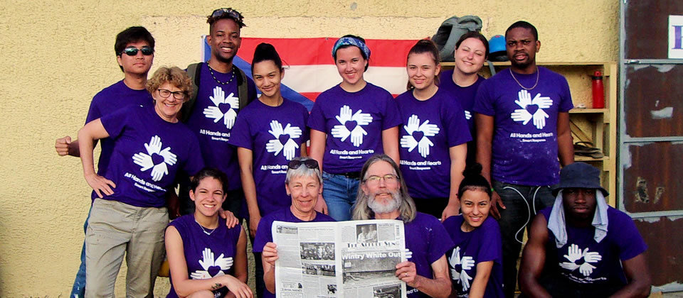 students wearing purple shirts holding a newspaper