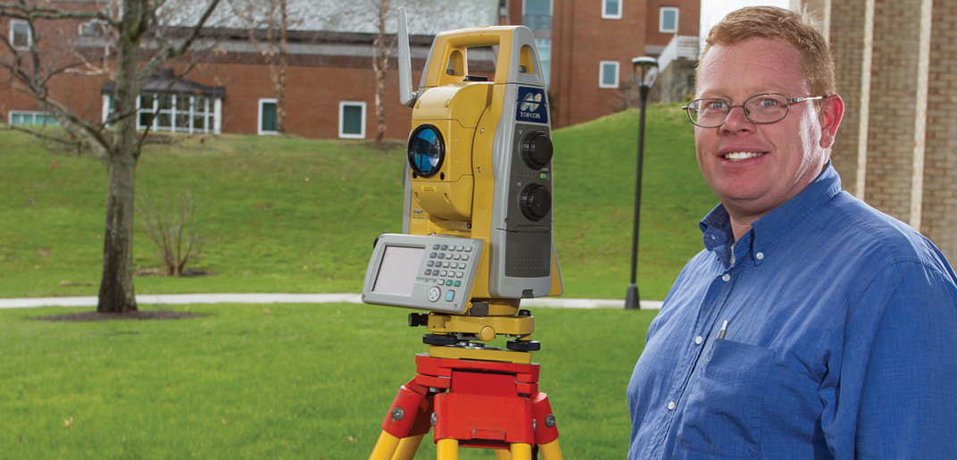 Roger O'Toole next to surveying equipment