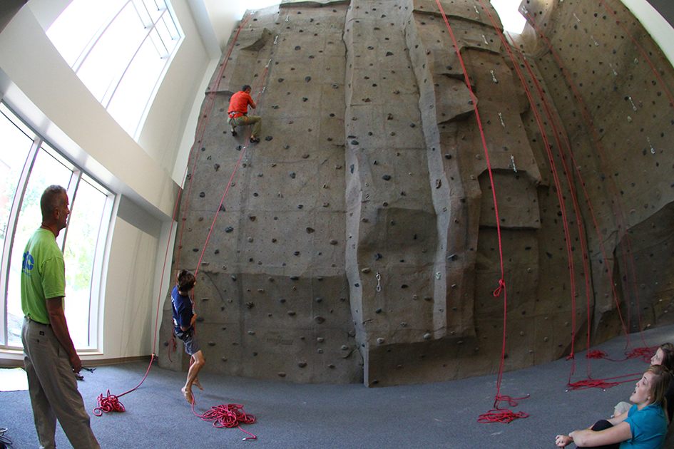 students climbing the rock climbing wall