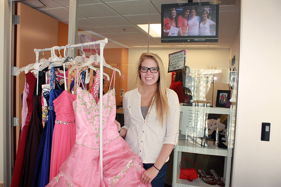 female student next to a rack of prom dresses