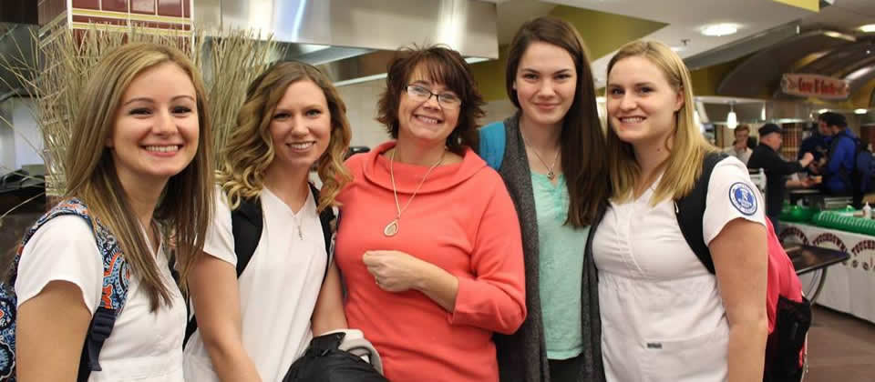 four female nursing students with their professor at the dining hall