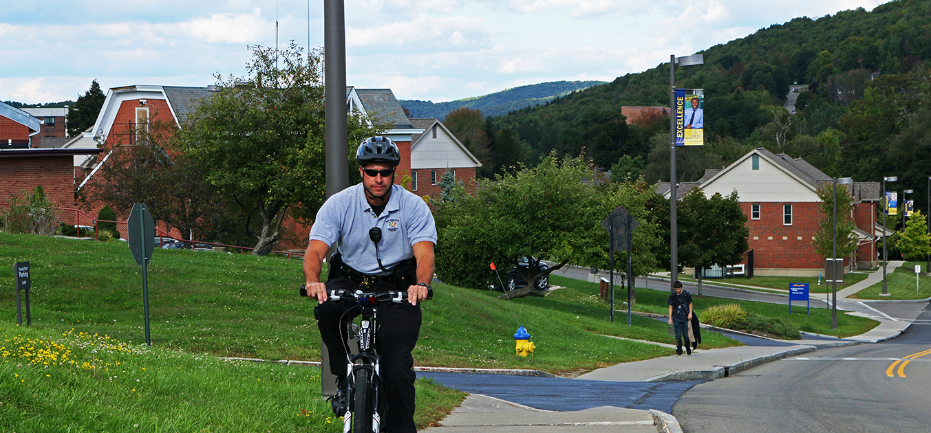 police officer riding up a bike up campus loop