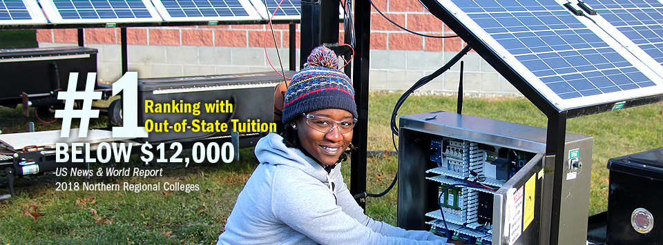 #1 ranking with Out-of-State Tuition Below $12,000 - US News & World Report, 2018 Northern Regional Colleges. Image of electrical trades student wearing winter hat working on solar panel power box.