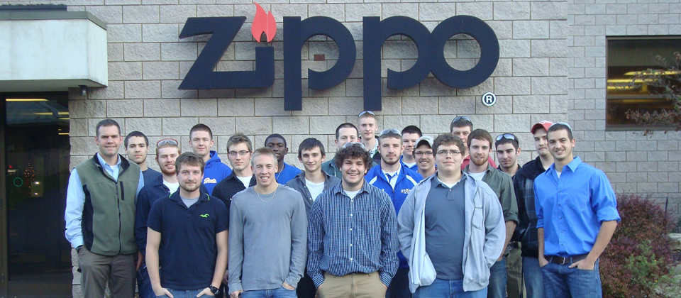 group of students standing in front of the Zippo logo