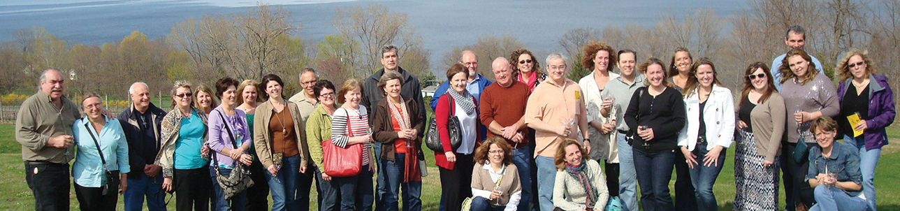 Large group of alumni holding Alfred State Alumni banner during recent cemetery clean up.