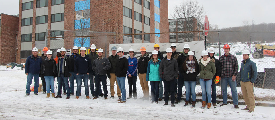 students standing outside of MacKenzie Complex with hard helmets on
