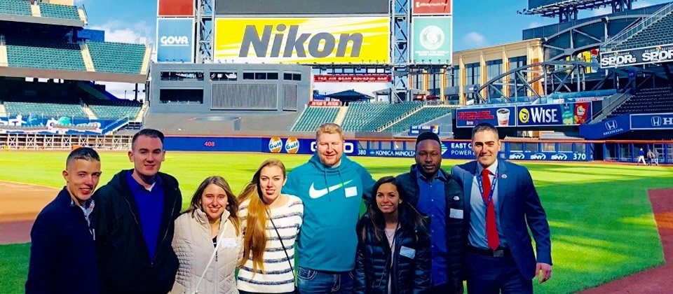 several students standing in front of the Citi Field stadium scoreboard