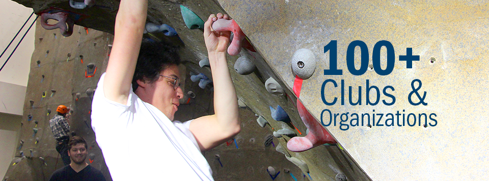 100+ Clubs and Organizations. Image of students climbing the rock walll in the Student Leadership Center.