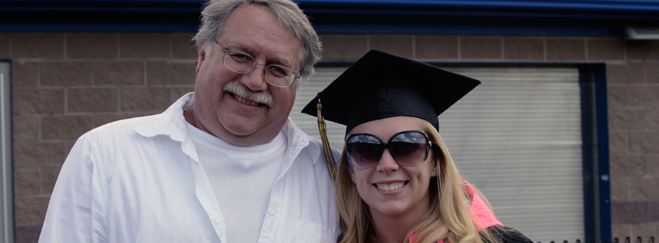 father with daughter, daughter wearing commencement cap and sunglasses