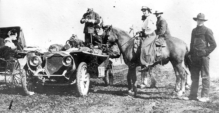old black & white photo someone in a car and someone on a horse