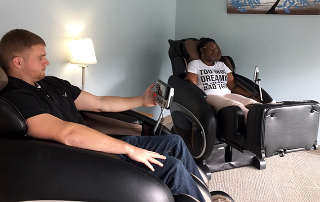 2 students in massage chairs at the Oasis
